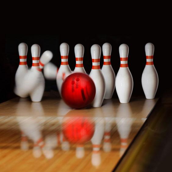 Red Bowling Ball Striking Bowling Pins