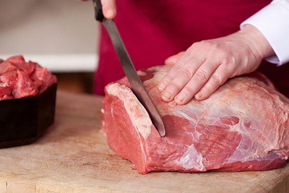 Butcher Cutting Raw Meat