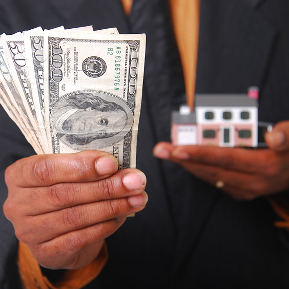 Man Holding a Miniature House and US Currency
