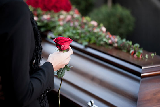 Woman Holding a Red Rose at a Funeral