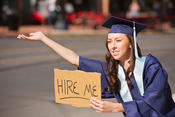 Female College Graduate Holding a 'Hire Me' Sign