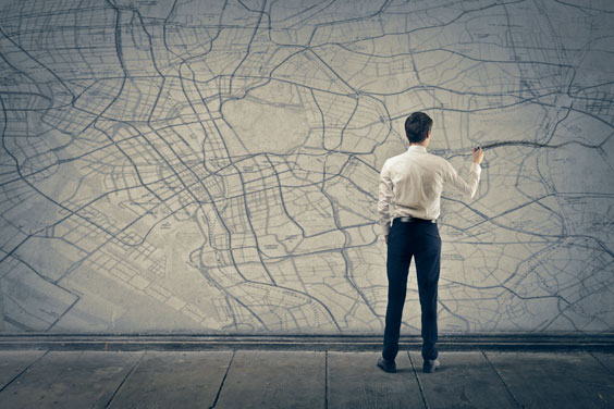 Man Marking a Route on a Map