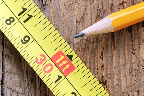 Tape Measure and Pencil on a Wooden Board