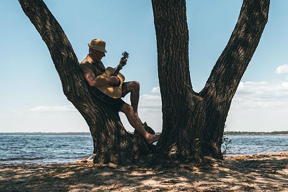 Senior Man Strumming his Guitar at the Beach
