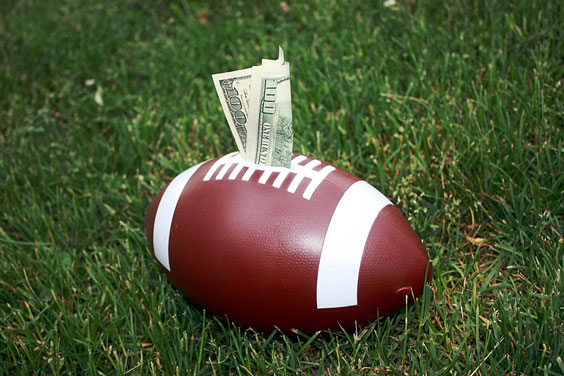 Football and One Hundred Dollar Bill on a Green Lawn