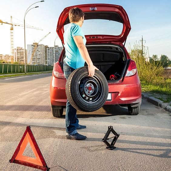Man Holding Spare Wheel and Tire