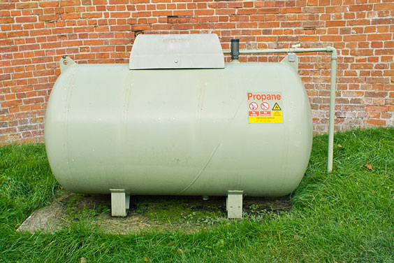 Propane Tank Next to a Brick Wall